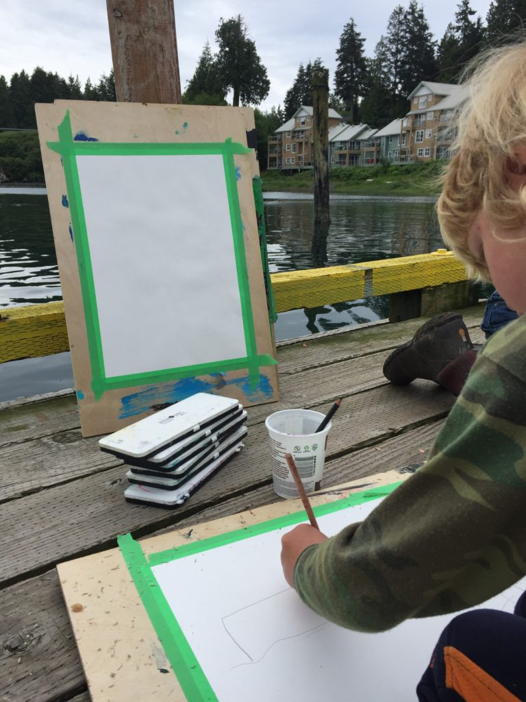 young artist at work with pencils, paint easel