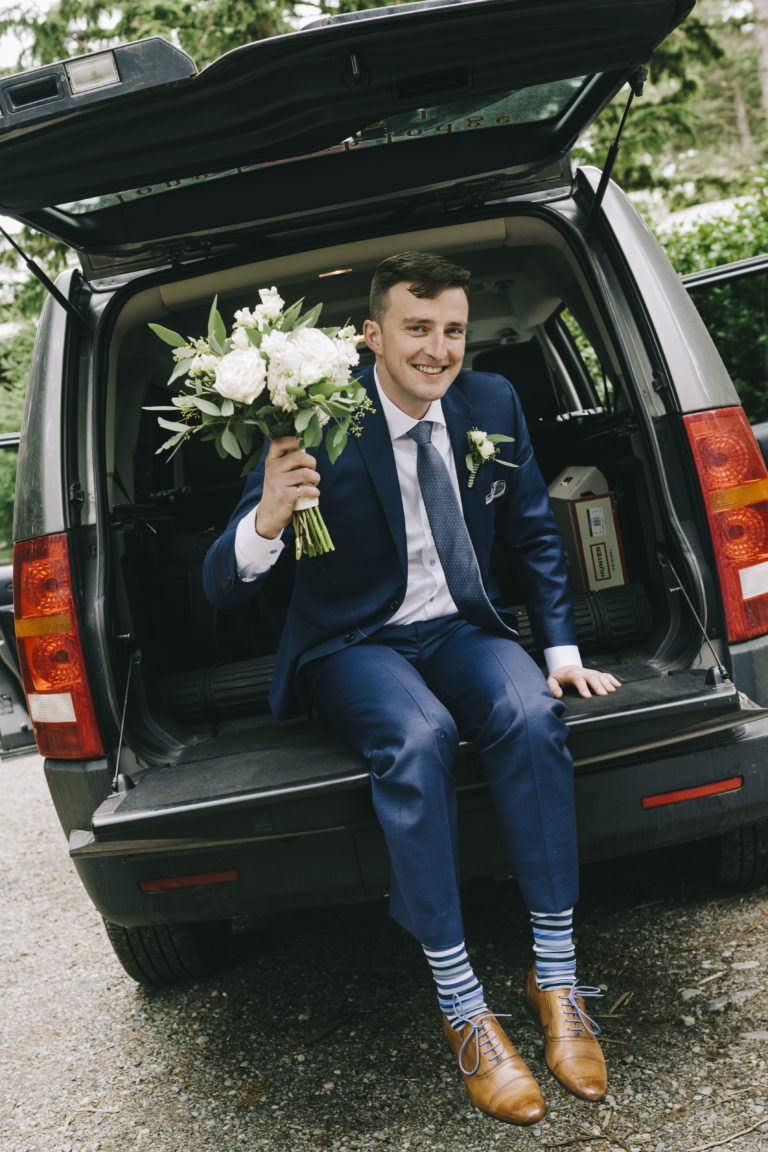 Tofino Wedding Photo Co. of wedding dude in car holding flowers