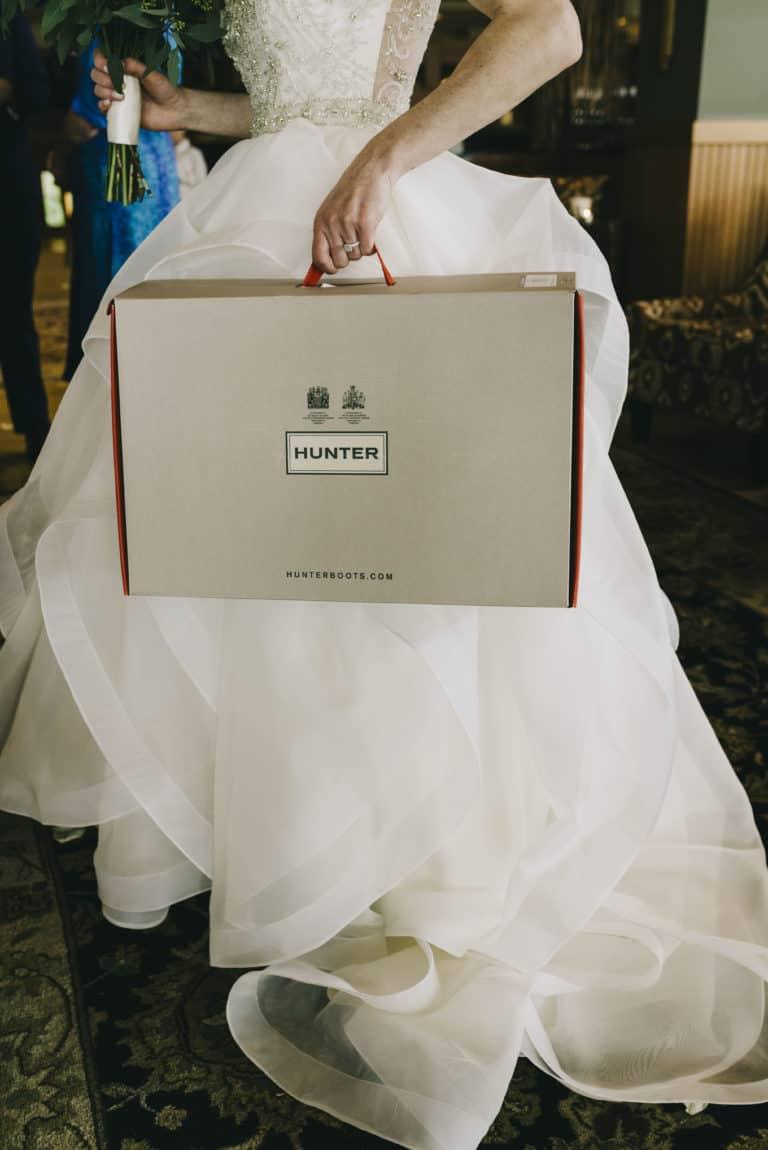 Tofino Wedding Photo Co. Bride carrying Hunter Boot box.